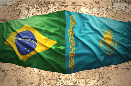 Waving Kazakh and Brazilian flags of the political map of the world photo
