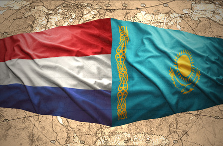 Waving Kazakh and Dutch flags of the political map of the world photo