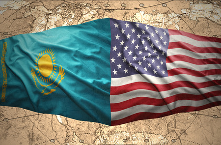 Waving Kazakh and American flags of the political map of the world photo