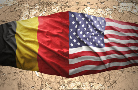 Waving Belgian and American flags of the political map of the world photo