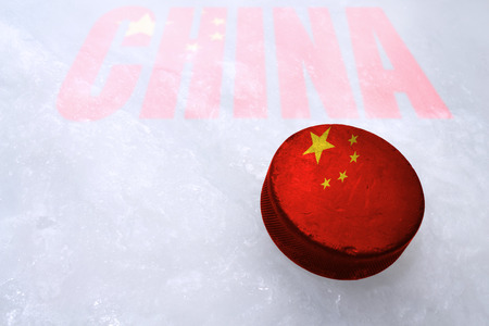 champ: Vintage old hockey puck with the China flag is on the ice Stock Photo