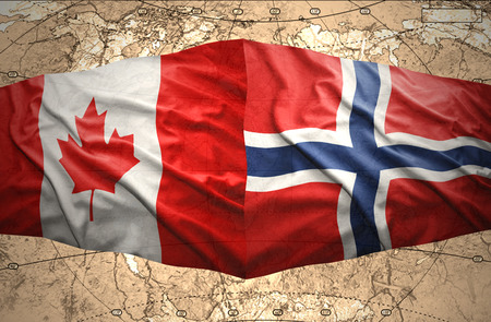 Waving Norwegian and Canadian flags of the political map of the world photo