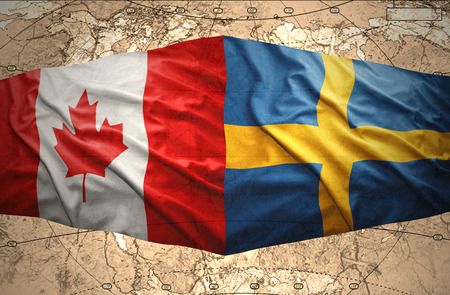 Waving Swedish and Canadian flags of the political map of the world photo