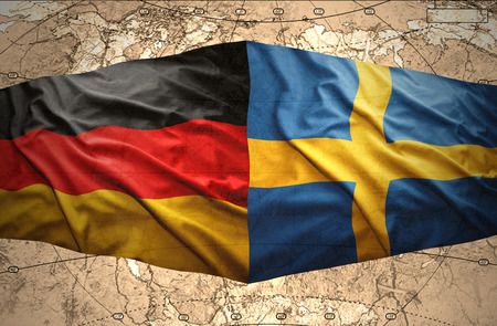 Waving Swedish and German flags of the political map of the world photo