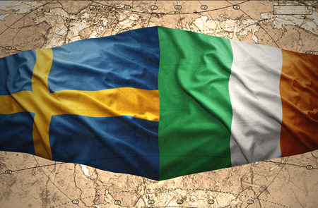 Waving Swedish and Irish flags of the political map of the world photo