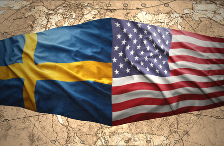 Waving Swedish and American flags of the political map of the world photo