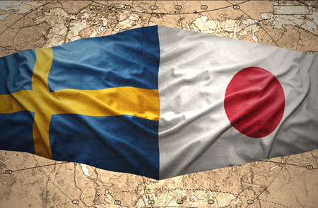 Waving Swedish and Japanese flags of the political map of the world photo