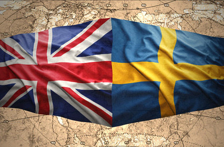 Waving Swedish and British flags of the political map of the world photo