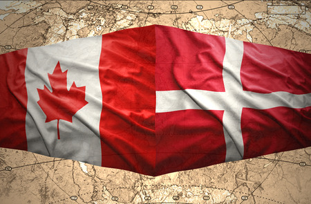 Waving Danish and Canadian flags of the political map of the world photo