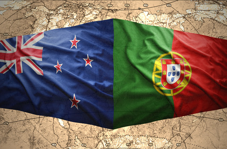 Waving New Zealand and Portuguese flags of the political map of the world photo