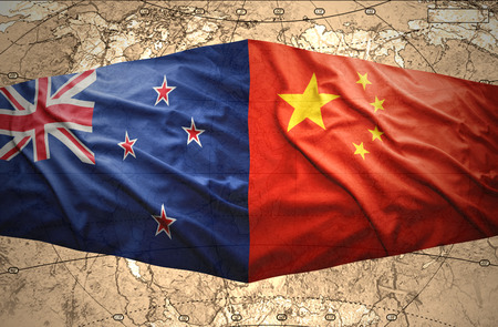 Waving New Zealand and Chinese flags of the political map of the world photo
