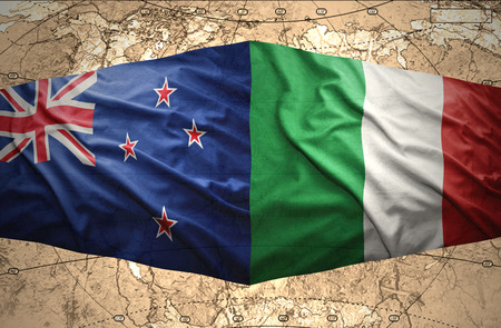 Waving New Zealand and Italian flags of the political map of the world photo