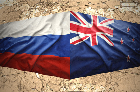 Waving New Zealand and Russian flags of the political map of the world photo