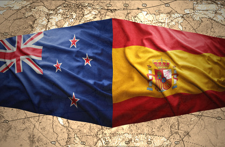 Waving New Zealand and Spanish flags of the political map of the world photo