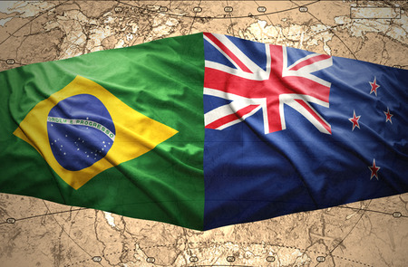 Waving New Zealand and Brazilian flags of the political map of the world photo
