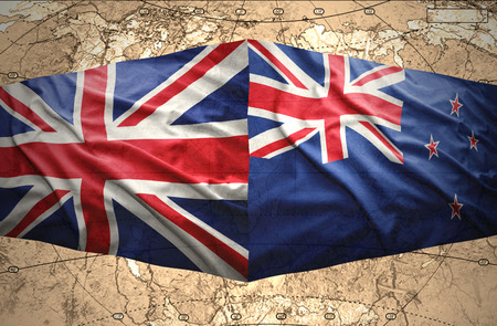 Waving New Zealand and British flags of the political map of the world photo