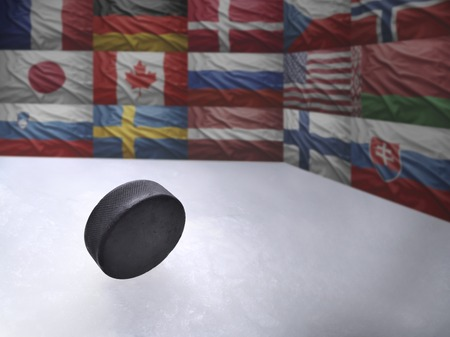Vintage old hockey puck is on the ice near national flags of famous hockey countries photo