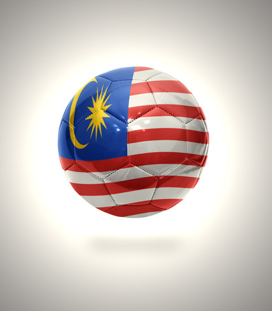 Football ball with the national flag of Malaysia on a gray background photo