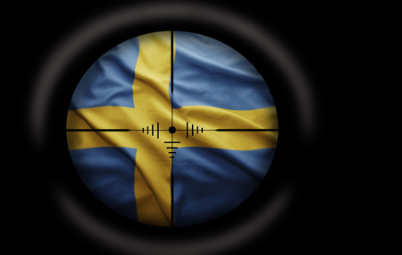 Sniper scope aimed at the Swedish flag photo