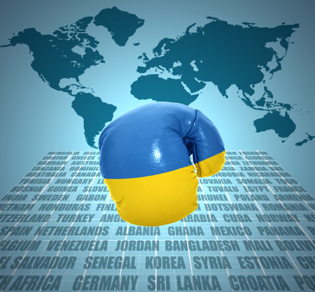 Boxing glove with the flag of Ukraine in motion on world map background photo