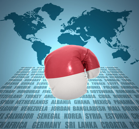 Boxing glove with the flag of Indonesia in motion on world map background photo