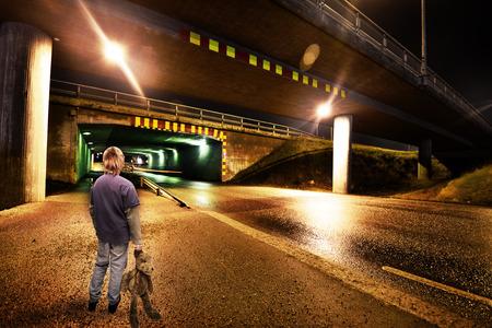 soltería: Niño de pie en una calle solitaria oscuridad en la n con un oso de peluche en la mano