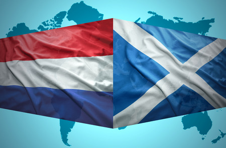 Waving Scottish and Dutch flags of the political map of the world photo