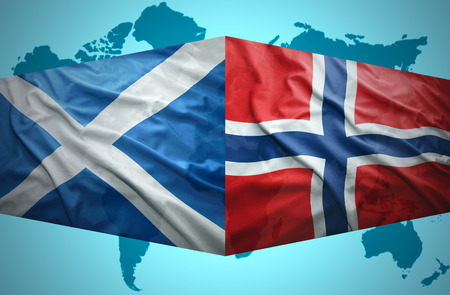 Waving Scottish and Norwegian flags of the political map of the world photo