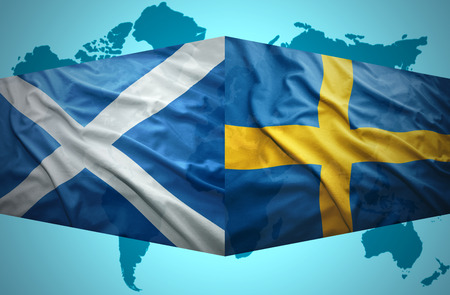 Waving Scottish and Swedish flags of the political map of the world photo