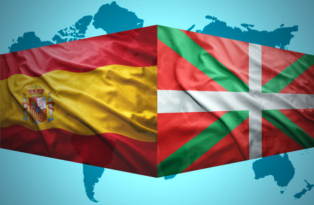 Waving Basque Country and Spanish flags of the political map of the world photo