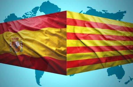 Waving Catalonia and Spanish flags of the political map of the world photo