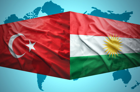 Waving Kurdish and Turkish flags of the political map of the world photo