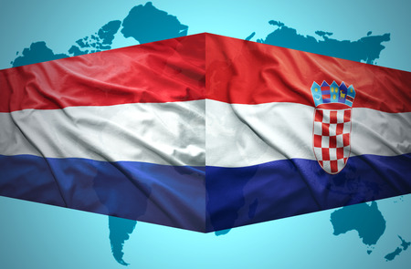 Waving Croatian and Dutch flags of the political map of the world photo