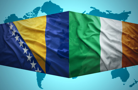 Waving Bosnian and Irish flags of the political map of the world photo