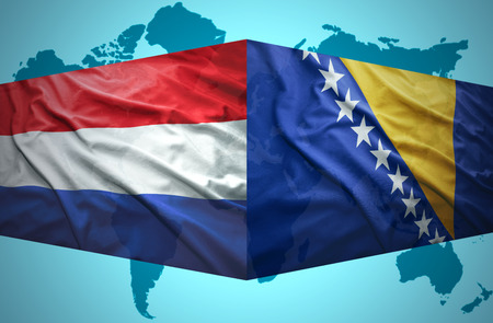 Waving Bosnian and Dutch flags of the political map of the world photo