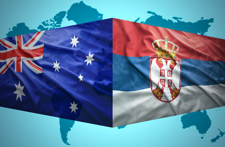 Waving Serbian and Australian flags of the political map of the world photo