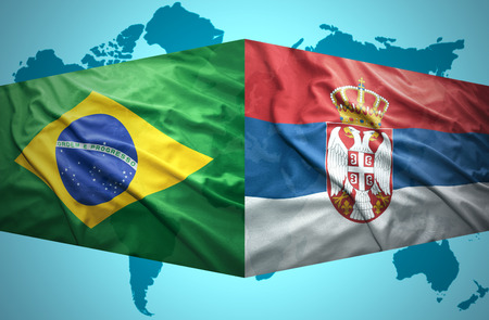 Waving Serbian and Brazilian flags of the political map of the world photo