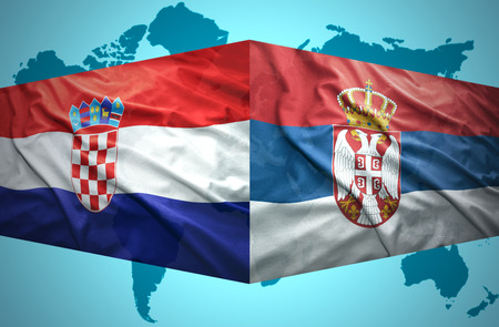 Waving Serbian and Croatian flags of the political map of the world photo