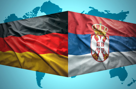 Waving Serbian and German flags of the political map of the world photo