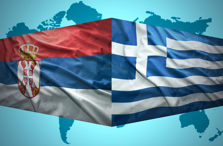 Waving Serbian and Greek flags of the political map of the world photo