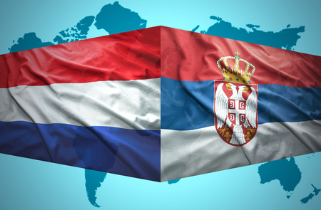 Waving Serbian and Dutch flags of the political map of the world photo