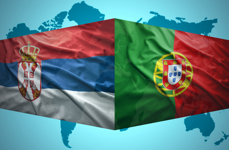 Waving Serbian and Portuguese flags of the political map of the world photo