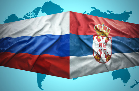 Waving Serbian and Russian flags of the political map of the world photo