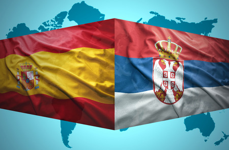 Waving Serbian and Spanish flags of the political map of the world photo