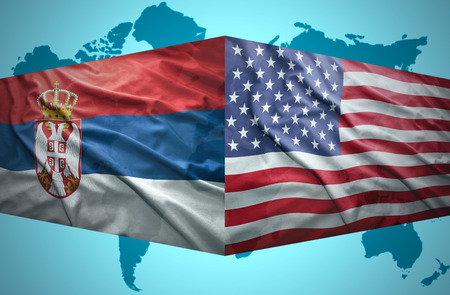 Waving Serbian and American flags of the political map of the world photo