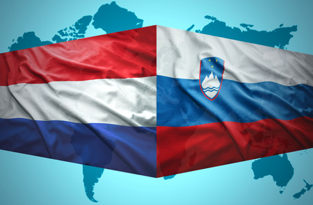 Waving Slovenian and Dutch flags of the political map of the world photo