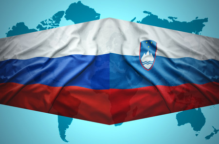 Waving Slovenian and Russian flags of the political map of the world photo
