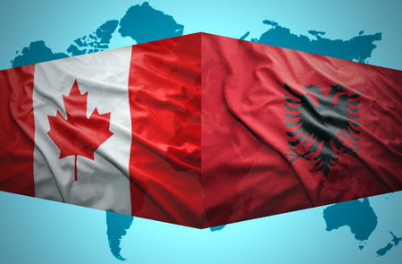 Waving Albanian and Canadian flags of the political map of the world photo