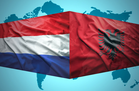 Waving Albanian and Dutch flags of the political map of the world photo