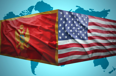 Waving Montenegrin and American flags of the political map of the world photo